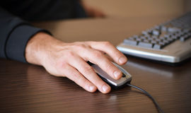 Male hand on mouse. Hand of a man working at computer clicking on mouse on dark desktop Royalty Free Stock Photo