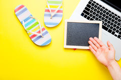 Male hand near blackboard, sandals and laptop. Photo of male hand near empty blackboard, colorful sandals and cool laptop on the wonderful yellow studio Royalty Free Stock Image