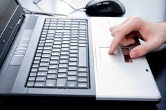 Male hand on notebook touchpad Stock Image