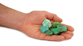 Male hand offering selection of heart chakra green healing stones royalty free stock photography