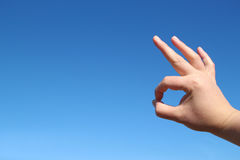 Male hand okay gesture in the blue sky Royalty Free Stock Photo