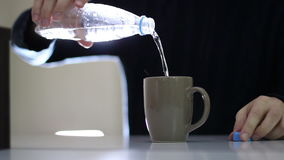 Male hand open a bottle of water and poured into the cup. It is a gray cup on the table stock footage