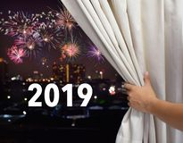 Male hand open the window curtain and see firework on night city sky background , celebration new year 2019 stock image