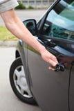 Male hand opening car door. Caucasian man opening car door of black land vehicle Stock Image