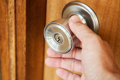 Male hand opening shining metal door handle Stock Photo