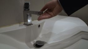Male hand opening tap in bathroom, no water supply due to utility arrears. Stock footage stock video footage