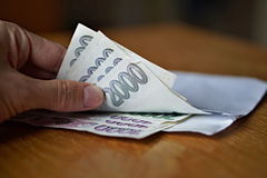 Male hand opening a white envelope full of Czech currency (Czech Crowns, CZK, Kc) on the wooden table as a symbol of cash transfer stock image
