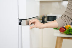 Male hand is opening white refrigerator door.  Royalty Free Stock Photos