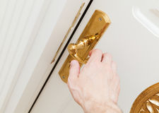 Male hand opens white door with golden handle Stock Photo