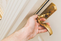 Male hand opens white wooden door Royalty Free Stock Image