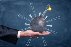 A male hand palm up holding a round iron bomb with a lit fuse on chalkboard background. Solve all trouble. Crisis management. Problem solving Royalty Free Stock Photo