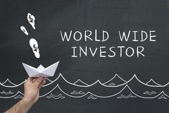 World wide investor on chalkboard. Male hand with paper boat and text on chalkboard: World wide investor Royalty Free Stock Photos