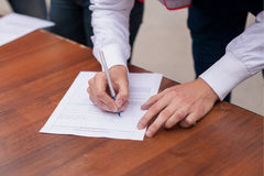Male hand with pen filling in the personal information form. Business man at work. Royalty Free Stock Images