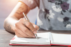 Male hand with pen writing on the notebook. Male hand with pen writing on the notebook Royalty Free Stock Photos