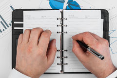 Male hand with pen wrote in a diary Royalty Free Stock Images