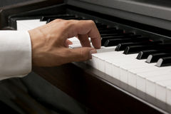 Male hand on a piano. Male hand playing on piano keys Royalty Free Stock Images