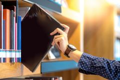 Male hand picking black book in library. Male hand choosing and picking black book in public library, education research and self learning in university life Stock Images