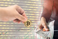 Male hand picking physical version of Bitcoin new virtual money. And female hand giving dollar cash on binary code and stock trading graph background Royalty Free Stock Photography