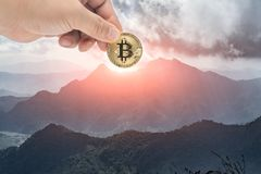 Male hand picking physical version of Bitcoin new virtual money. Form the mountain,Mountains like trading graphs.Cryptocurrency investment concept Stock Images