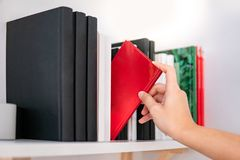 Male hand picking red book on bookshelf. Male hand choosing and picking red book on white bookshelf in public library. Education research and self learning in Stock Photos