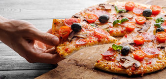 Male hand picking tasty pizza slice. Male hand picking tasty pizza slice stock photos