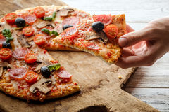 Male hand picking tasty pizza slice. royalty free stock photography