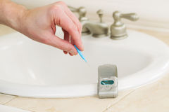 Male hand picking up dental tooth pick to clean his teeth Stock Photography