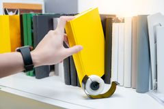 Male hand picking yellow book on bookshelf. Male hand choosing and picking yellow book on white bookshelf in public library. Education research and self learning Stock Photo