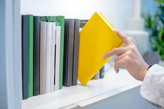 Male hand picking yellow book on white bookshelf. Male hand choosing and picking white book on white bookshelf in public library, education research and self Stock Photos
