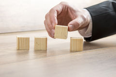 Male hand placing four wooden cubes in a row. Stock Images