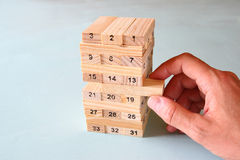 Male hand placing wooden block on a tower. planing and strategy concept Stock Images