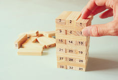 Male hand placing wooden block on a tower. planing and strategy concept Stock Photos