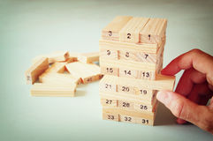 Male hand placing wooden block on a tower. planing and strategy concept Royalty Free Stock Photo