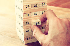 Male hand placing wooden block on a tower. planing and strategy concept Royalty Free Stock Image