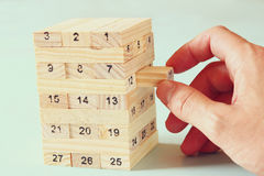 Male hand placing wooden block on a tower. planing and strategy concept Stock Photography
