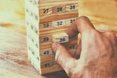 Male hand placing wooden block on a tower. planing and strategy concept Royalty Free Stock Images