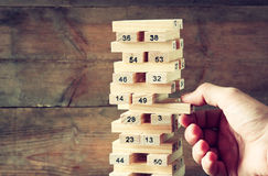 Male hand placing wooden block on a tower. planing and strategy concept Royalty Free Stock Photography