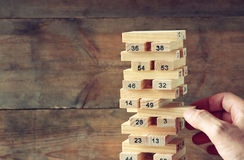 Male hand placing wooden block on a tower. planing and strategy concept Stock Photo