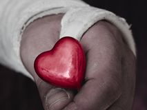 Male hand in plaster cast holding small glossy red heart. royalty free stock photo