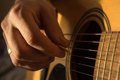 Male hand playing acoustic guitar in natural light. Male hand playing acoustic guitar stock photo