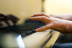 Male hand playing the piano. Closeup of hands playing piano Royalty Free Stock Photo