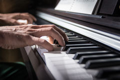 Male hand playing piano. Male hand playing the keys of piano Stock Photo