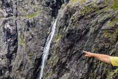 Male hand pointing at mountains waterfall. Male hand showing at mountains landscape with waterfall, travel concept Royalty Free Stock Photography