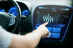 Male hand pointing to diagram on screen in car Royalty Free Stock Photo