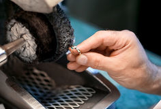 Male hand is polishing a wedding ring Royalty Free Stock Photo