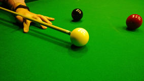Male hand with a pool cue preparing to hit the white ball Royalty Free Stock Photography