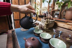 Male hand pouring tea into tea cups in store Stock Photo