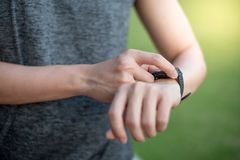 Male hand pressing button menu on smart watch after running. Male hand pressing button menu on smart watch checking heart rate on monitor after jogging in the Royalty Free Stock Image