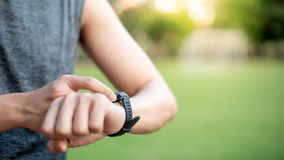 Male hand pressing button menu on smart watch after running. Male hand pressing button menu on smart watch checking heart rate on monitor after jogging in the Stock Image