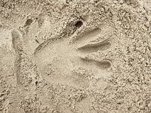 Male hand print in the salt sand on the beach. Long fingers hand Stock Images